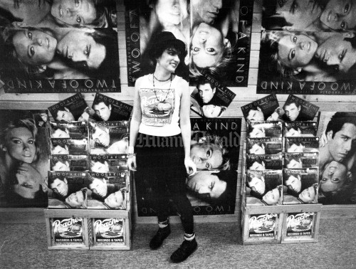 "1/19/1984, Miami Herald Staff: Rose Ortiz, has worked at Peaches Records and Tapes store for about 5 months. She is seen in front of a John Travolta/Olivia Newton-John display. Fancy displays of multiple images are used in Peaches. The store was one of the seven in South Florida's ""record store rows"". The row, which extends from North Miami Beach Boulevard from I-95 to NE 15th Avenue, houses Open Books and Records; Peaches; Record Liquidators, 87 NE 167th St.; Vibrations, 269 NE 167th St.; Discount Records, 1364 NE 163rd St.; Spec's Music, 1205 NE 163rd St.; and Record Land."